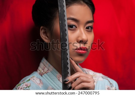 Aggressive beauty. Young beautiful Japanese woman in kimono looking at camera and holding katana sword by her face while standing against red background - stock photo