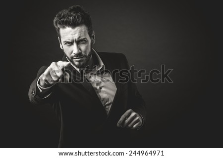 Aggressive businessman pointing finger against dark background - stock photo
