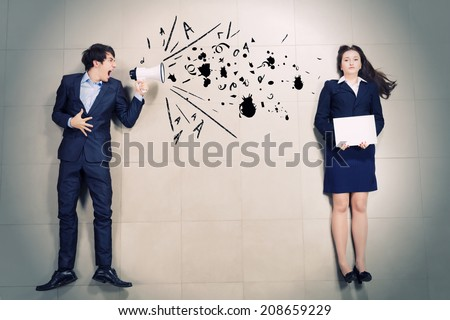 Aggressive businessman shouting at colleague with megaphone - stock photo