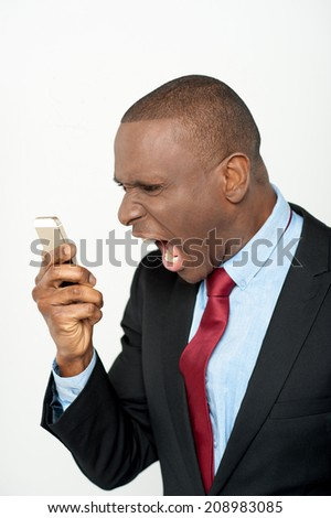 Aggressive businessman yelling into a cellphone - stock photo