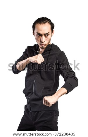 Aggressive fighter in hood while punching against white background - stock photo