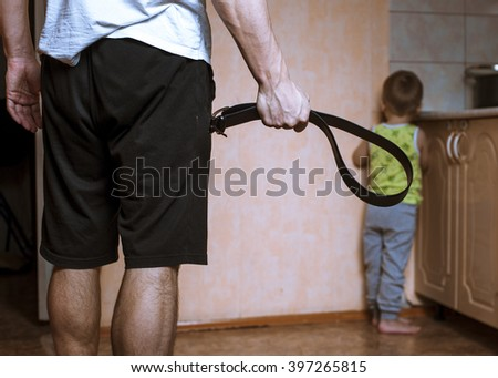 Aggressive parent with belt and frightened child in corner. Domestic violence. - stock photo
