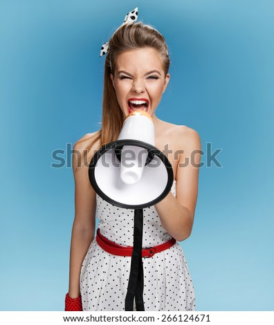 Aggressive pin-up girl screaming with megaphone, mouthpiece, speaking trumpet. Film making or film production concept / photo set of young American pin-up model on blue background - stock photo