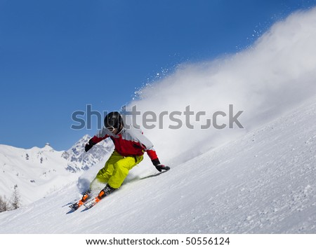 Aggressive skier in the snow  powder skiing fast - stock photo