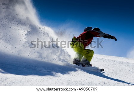 Aggressive skier making snow  powder while turning and skiing fast - stock photo
