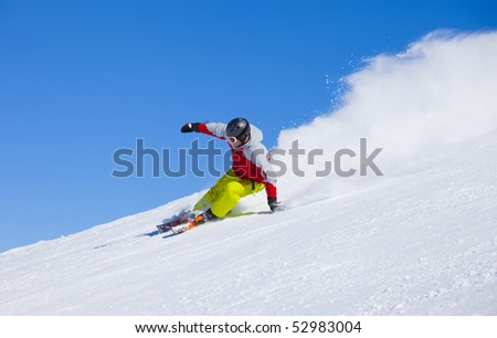Aggressive sport skier in the snow powder skiing fast - stock photo