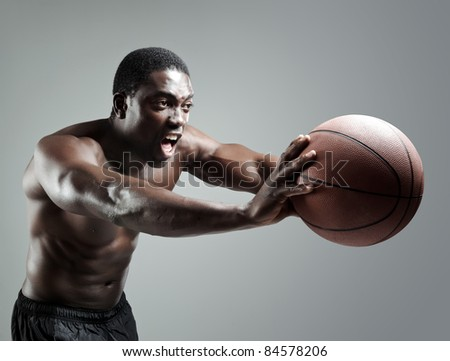Aggressive sportsman in the studio passing a basketball - stock photo
