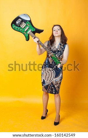 aggressive woman staying with electric guitar - stock photo