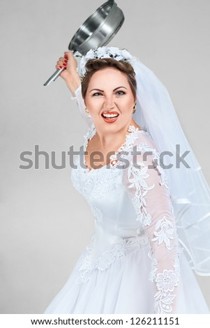 Aggressive young bride with a frying pan attack - stock photo