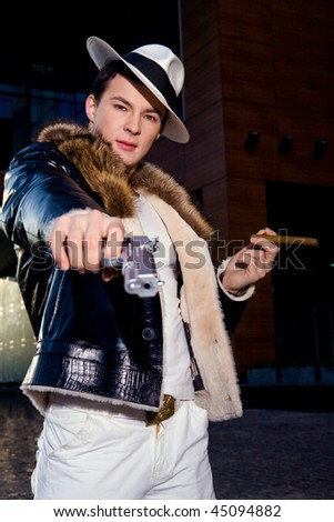 Aggressive young gangster with a gun and cigar aiming at camera outdoors