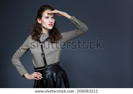 Aggressive young girl posing in studio in military shirt and leather skirt