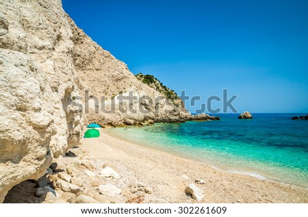 Agia Eleni beach Kefalonia, Greece. People relaxing on one of the most beautiful rocky wild beaches of Kefalonia. - stock photo