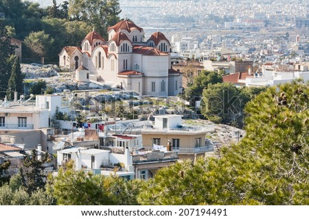 Agia Marina or Saint Marina orthodox church on the Hill of the Nymphs in Athens, Greece, with the city in the background.