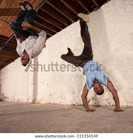 Agile capoeria martial artists perform acrobatic techniques - stock photo