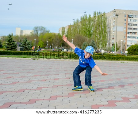 Agile young boy in a trendy blue outfit doing cartwheels in a paved urban square balancing on his hands