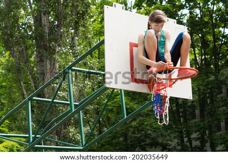 Agile young girl fixing a net on a basketball goal post sitting on top of the metal hoop attaching it with her hands