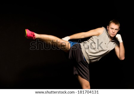 Agile young kickboxer lashing out with his foot while watching intently ready to follow up with a punch on a dark background - stock photo