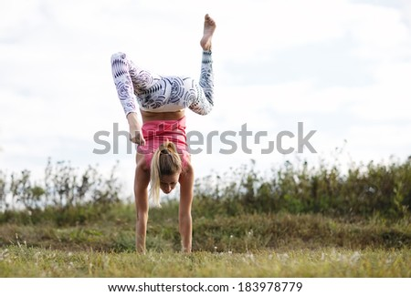 Agile young woman doing a handstand outdoors in the countryside balancing on her hands with her legs bent in opposite directions - stock photo