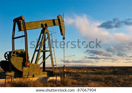 "Aging pump rig standing alone against the prairie of western colorado, ""sunset on oil"" depicts the fading fossil fuel extraction industry today. - stock photo"