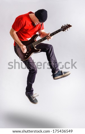 Aging rocker in sun glasses, t-shirt, blue trousers and with guitar jumping