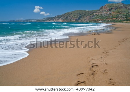 Agios Nikolaos beach from Crete, Greece. Footprints in the sand. Sea on the left mountains in the back. - stock photo