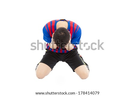 agitated soccer player kneel down and  cover his face to cry - stock photo