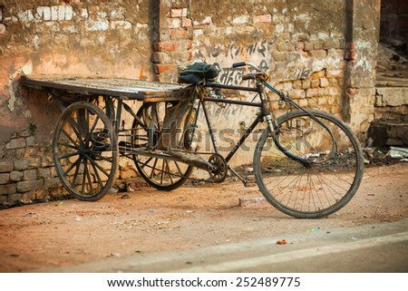 AGRA, INDIA - CIRCA NOV 2012: An improvised tricycle with a wooden cargo pallet, parked against an old brick wall in Agra, India. - stock photo