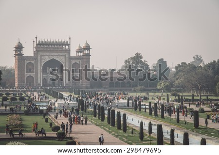 AGRA, INDIA - 28 FEBRUARY 2015: AGRA, INDIA - 28 FEBRUARY 2015: View of North side of Great Gate from Taj Mahal with visitors. Post-processed with grain, texture and colour effect. - stock photo