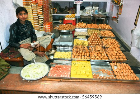 AGRA, INDIA - FEBRUARY 22:Vendor always sits in lotus position while sells goods in Indian shops. February 22, 2008.Agra, India. - stock photo