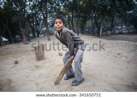 AGRA, INDIA - JANUARY 8, 2015: Little Indian boy playing game on January 8, 2015 in Agra, India - stock photo