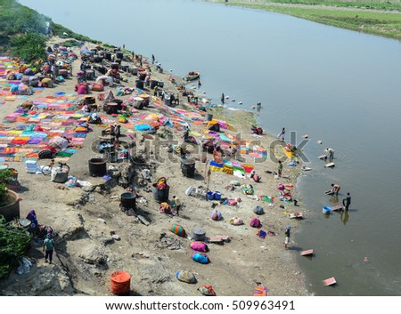Agra, India - Jul 13, 2015. People washing and drying cloth on the sandy banks of Yamuna river, Agra, India.