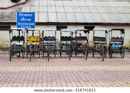 AGRA, INDIA - JULY 19, 2015: Rickshaws park in rickshaw stand. The pedal-powered rickshaws are cheap and environment friendly, Agra, India. JULY 19 2015 - stock photo