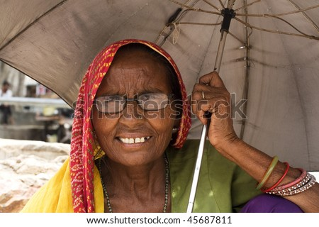 AGRA, INDIA - JUNE 18: Portrait of a senior Indian woman stands in front of temple on June 18, 2008 in Agra, India. Local women wear colorful saree (sari) as traditional clothing. - stock photo