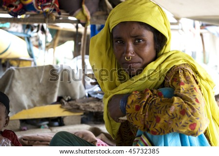 AGRA, INDIA - JUNE 19: Portrait of old tribal woman in a village in india, from Agra June 19, 2008 in Agra, India. Local women wear colorful saree (sari) as traditional clothing. - stock photo