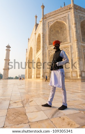 Agra, India - November 19, 2009: An unidentified Rajasthani Indian man in long white kurta shirt, red hat and large mustache standing outside atop the white marble base of the Taj Mahal