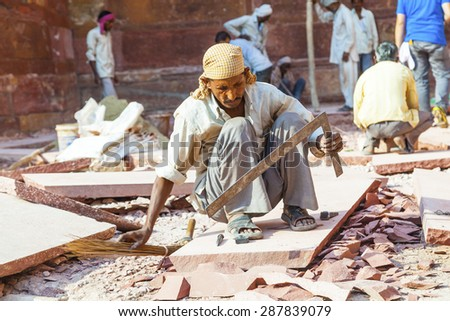 AGRA, INDIA - OCT 17, 2012: worker prepares sandstones for renovation of the Red Fort in Agra, India. The fort was mentioned for the first time in 1080 AD when a Ghaznavide force captured it. - stock photo