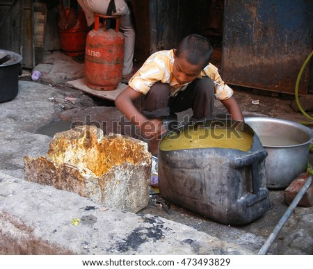 AGRA, INDIA, October 2012 - an unidentified boy cleans dishes behind the restaurant that can normally be seen along the little street in India #editorial