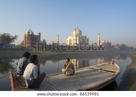 AGRA, INDIA - OCTOBER 28: Unidentified Indian boatmen await tourists along the banks of river Yamuna, which you can admire the Taj Mahal in Agra on October 28, 2007. - stock photo