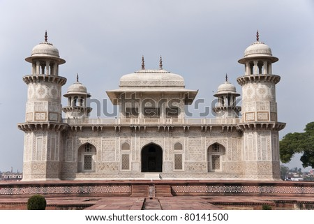 Agra's Baby Taj mausoleum against light blue skies in India Close up of the decorated white marble edifice on red stone platform.