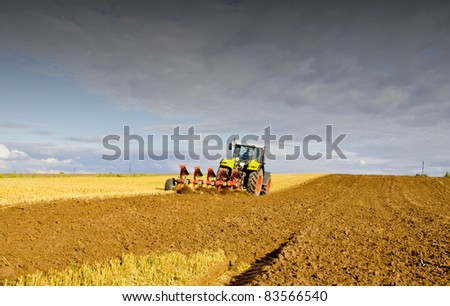 agrarian landscape with tractor after harvest - stock photo