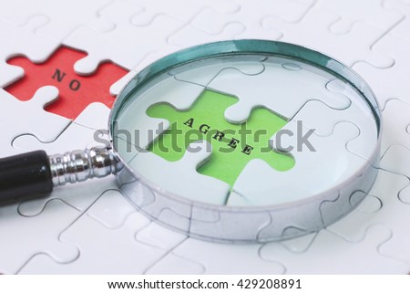 AGREE and NO puzzle with magnifier glass - stock photo