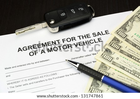 agreement form document for a Sale of motor vehicle with car key, money and pen - stock photo