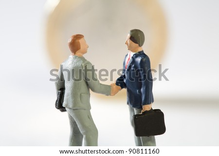 Agreement On New EU Fiscal Proposals. Two miniature models of businessmen shake hands on top of a Euro coin, conceptual.