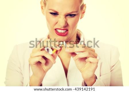 Agressive business woman breaking cigarette - stock photo