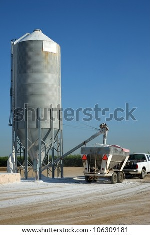 Agricultural chemicals are loaded from a storage tank into a trailer-mounted hopper on a Central California farm - stock photo
