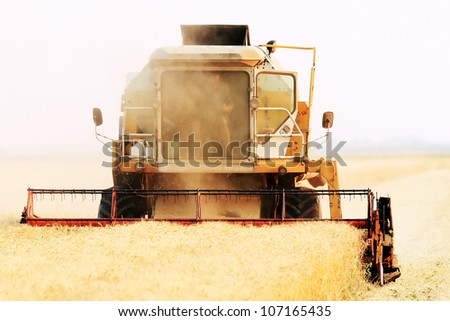 Agricultural combine in a field - stock photo