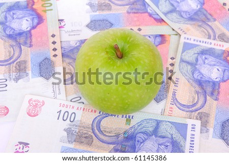 Agricultural concept: a single big green Granny Smith apple on South African currency (Rands) background.