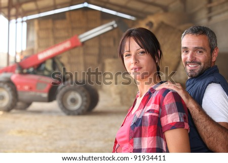 Agricultural couple in the barn with a tractor - stock photo