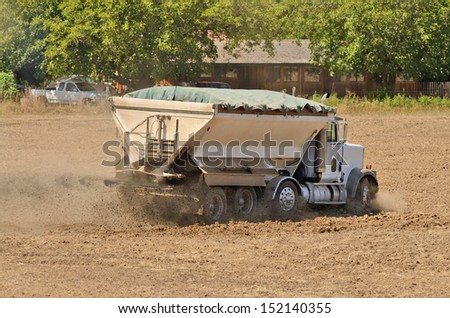 Agricultural fertilizer spreader working a newly plowed field in preparation for a new vineyard - stock photo