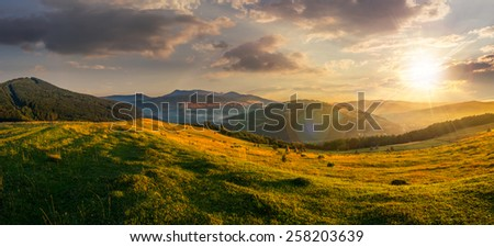 agricultural field on hillside in mountains near village in sunset light - stock photo